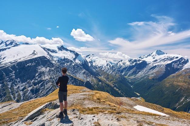 Giovane uomo in piedi su una scogliera che si affaccia sulla valle in nuova zelanda