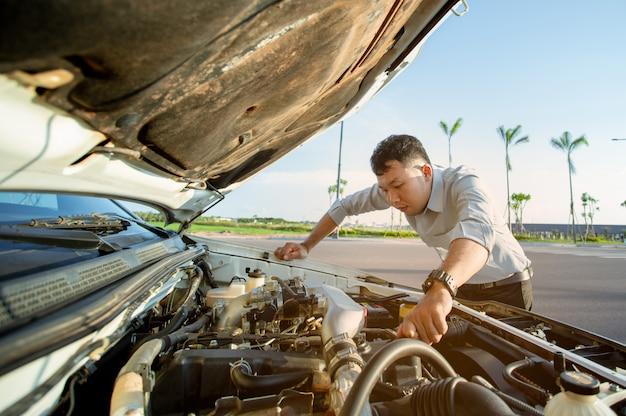Giovane uomo in piedi davanti alla sua macchina rotta e ha aperto il cofano per il controllo del motore
