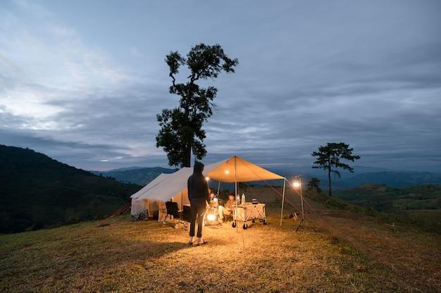 Giovane uomo in piedi e tenendo la lanterna brillare con gli amici seduti in una grande tenda sulla collina in campeggio in campagna.