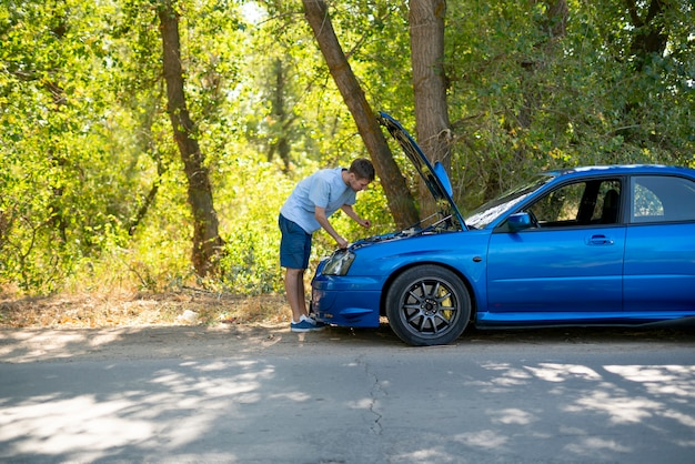 Un giovane in piedi vicino alla macchina con il cofano aperto e risolve alcuni problemi con il motore