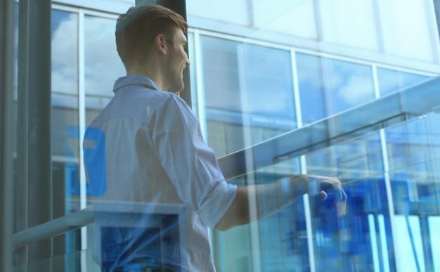 Giovane in piedi vicino alla finestra nel suo ufficio mentre pensa ai suoi obiettivi.