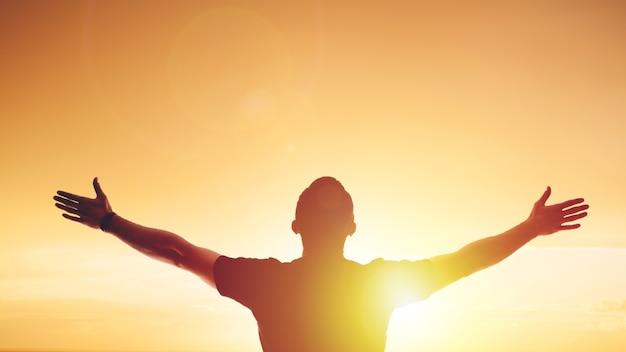 Giovane uomo in piedi teso al tramonto