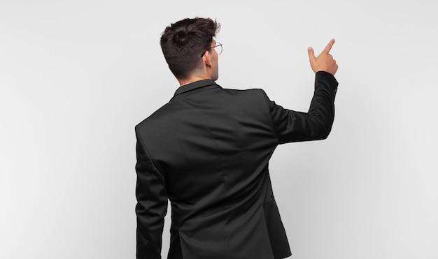 Giovane uomo in piedi e indicando un oggetto sullo spazio della copia, vista posteriore