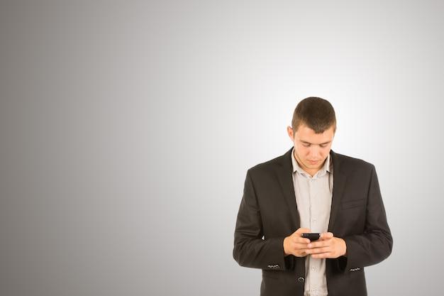 Giovane uomo in piedi che scrive sul suo cellulare