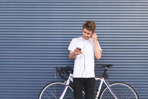 Il giovane fa una pausa una bicicletta bianca che ascolta la musica in cuffia e guarda lo smartphone