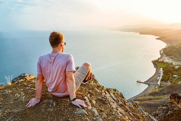 Un giovane si trova sul bordo di una scogliera al tramonto con un'incredibile vista sulle montagne