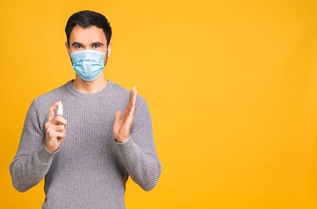 Giovane uomo in maschera facciale sterile in posa isolato su sfondo giallo.