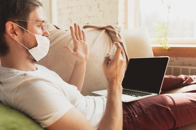 Giovane che studia a casa durante i corsi online per disinfettante, infermiere, servizi medici. ottenere la professione mentre si è isolati, quarantena contro il coronavirus. utilizzando laptop, smartphone, cuffie.