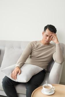 Giovane che soffre di mal di testa dopo una dura giornata di lavoro, seduto sul divano a casa, copia spazio