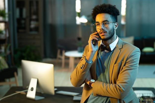 Il giovane in giacca e cravatta ha una conversazione sul suo telefono cellulare mentre lavora in ufficio