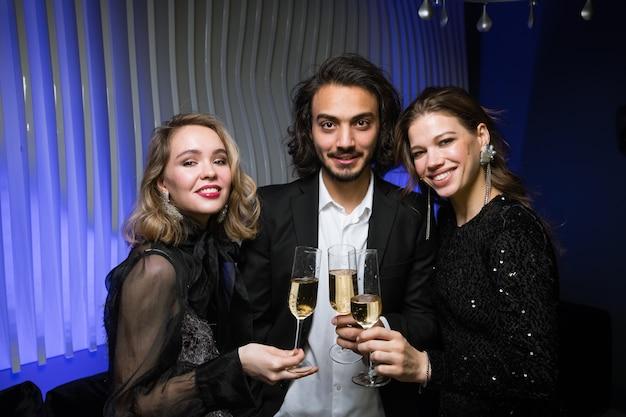 Giovane uomo in tuta in piedi tra due belle ragazze durante il brindisi di capodanno alla festa in discoteca
