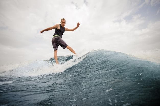 Giovane che pratica il surfing sul bordo giù l'acqua blu contro il cielo grigio