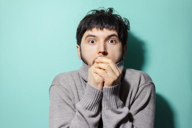 Giovane uomo in maglione scaldando le mani sul muro di colore aqua menthe.