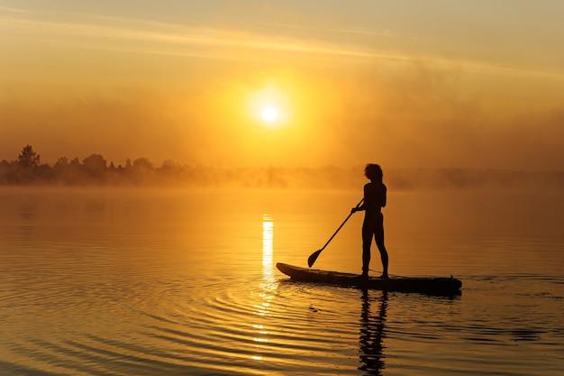 Giovane uomo in costume da bagno facendo surf a bordo di sup durante l'alba incredibile al lago locale.