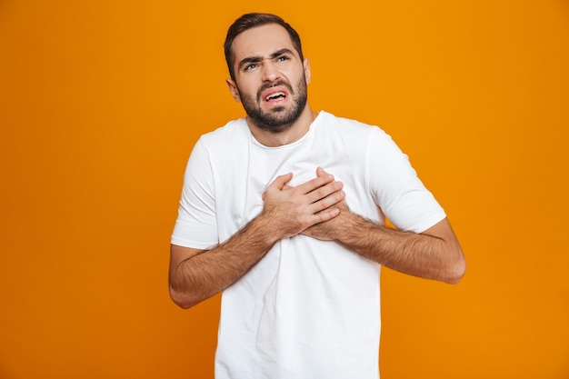 Giovane uomo in t-shirt toccando il suo cuore a causa del dolore mentre, isolato su giallo