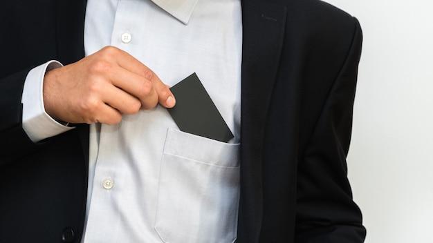 Il giovane tira fuori il biglietto da visita in bianco dalla tasca.