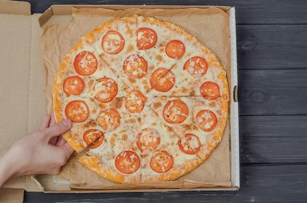 Un giovane prende una fetta di pizza con formaggio e pomodori in una scatola su uno sfondo di legno nero.
