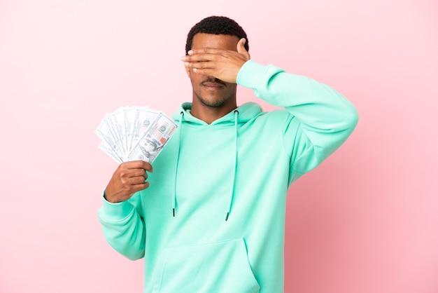 Giovane che prende un sacco di soldi su sfondo rosa isolato che copre gli occhi con le mani. non voglio vedere qualcosa