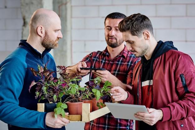 Giovane che cattura foto di piante verdi mentre ragazzo calvo che tiene scatola di legno con vasi di fiori e maschio con tablet imparando tipi di piantine