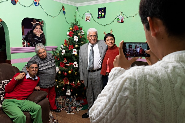 Un giovane che scatta una foto della sua famiglia davanti all'albero di natale a casa dei nonni