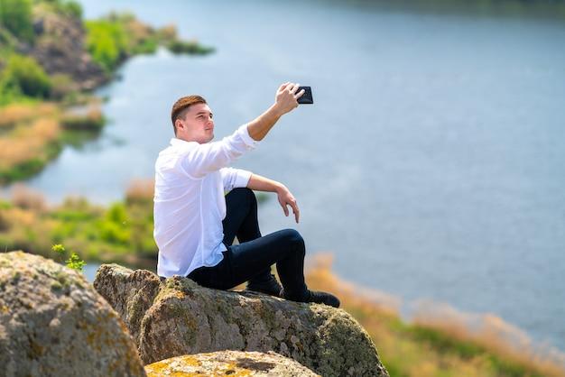 Giovane che cattura un selfie su un grande masso o roccia sopra un fiume in posa sul suo smartphone con un sorriso
