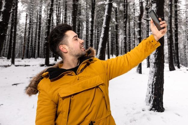 Giovane che cattura un selfie su un bosco innevato con una giacca a vento gialla
