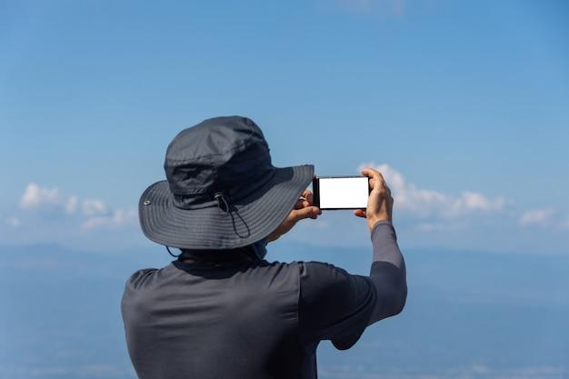 Giovane che prende selfie sulla cima di una montagna