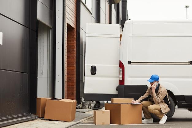 Giovane che comunica sul telefono cellulare e che effettua la consegna che si siede vicino al furgone con scatole all'aperto