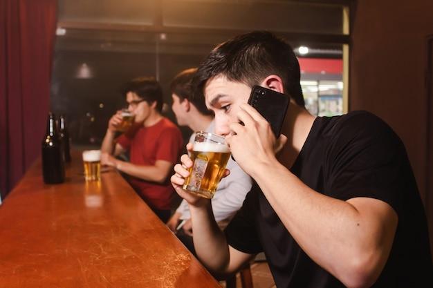 Un giovane che parla al telefono e beve birra mentre i suoi amici ubriachi chiacchierano al bar.