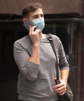Giovane che parla al telefono fuori mentre indossa una maschera medica