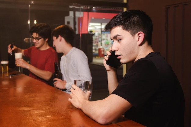 Un giovane che parla al telefono mentre i suoi amici si godono una birra al bar.