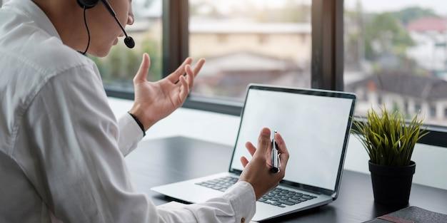 Giovane insegnante insegnante che indossa le cuffie parlando, tenendo lezione online. studente concentrato che guarda lo schermo del monitor del computer