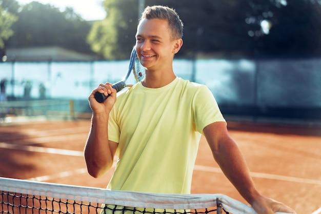 Adolescente del giovane con la racchetta da tennis in piedi vicino a rete sul campo da tennis in terra battuta