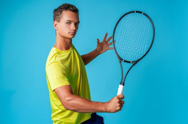 Giovane giocatore di tennis in abiti sportivi in posa su sfondo blu vicino