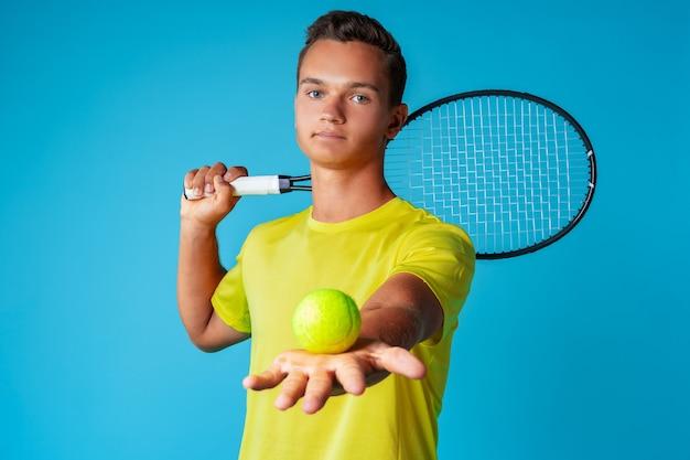 Giocatore di tennis del giovane in abiti sportivi che posano contro l'azzurro