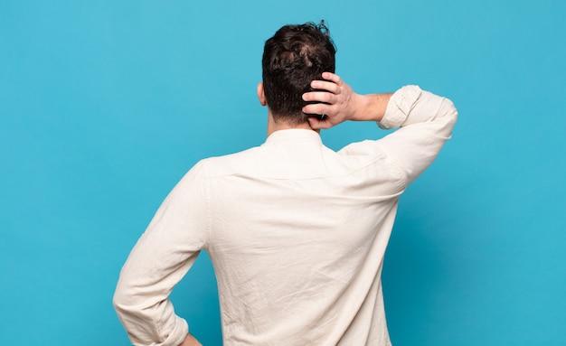 Giovane che pensa o dubita, grattandosi la testa, sentendosi perplesso e confuso, vista posteriore o posteriore