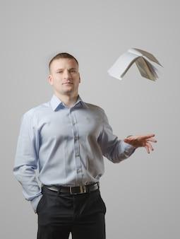 Un giovane getta il libro sopra la sua testa. su una superficie bianca