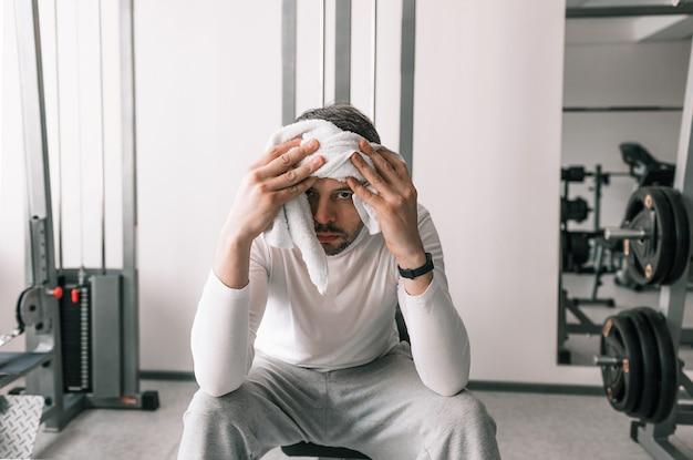 Un giovane stanco dopo un duro allenamento si siede e si asciuga il sudore dal viso con un asciugamano al club sportivo. recupero di riposo.