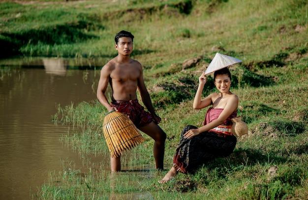Giovane uomo in topless in piedi e tenendo in mano una trappola da pesca in bambù per pescare pesce per cucinare con una bella donna seduta vicino alla palude