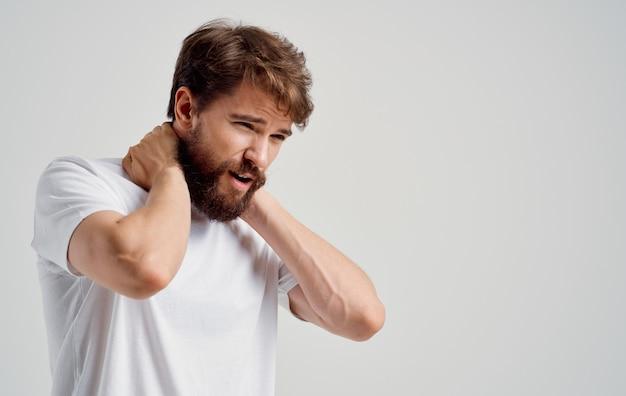 Giovane uomo toccare il collo con le mani dolore alla colonna vertebrale vista laterale modello ritratto