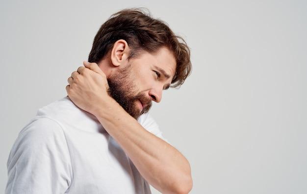 Giovane uomo che tocca il collo con le mani dolore alla colonna vertebrale vista laterale modello ritratto