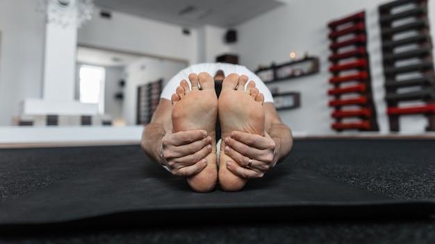 Istruttore del giovane che fa yoga all'interno. primo piano dei piedi nudi maschili.