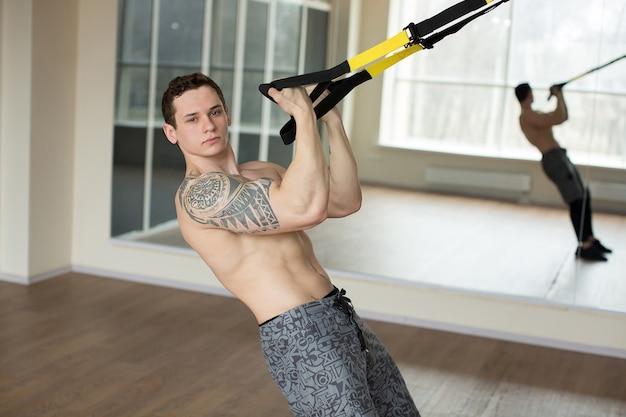 Giovane uomo allenamento esercizio push up con cinghie trx fitness in palestra