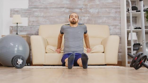 Muscolo del tricipite di formazione del giovane a casa facendo uso del sofà.