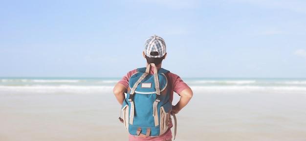 Viaggiatore giovane con zaino in spiaggia