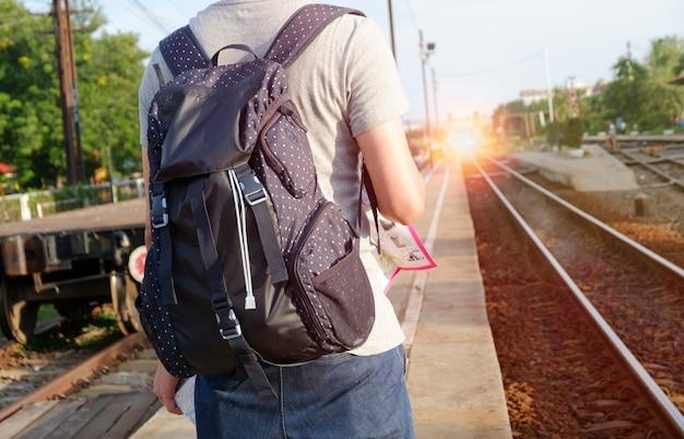 Viaggiatore giovane con zaino alla stazione ferroviaria con un concetto di viaggio, viaggi e ricreazione