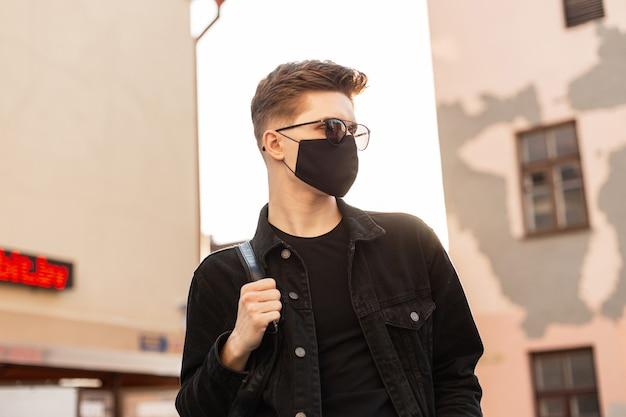 Il giovane con occhiali da sole alla moda in giacca di jeans con maschera nera protettiva si trova in città e si gode la luminosa giornata primaverile