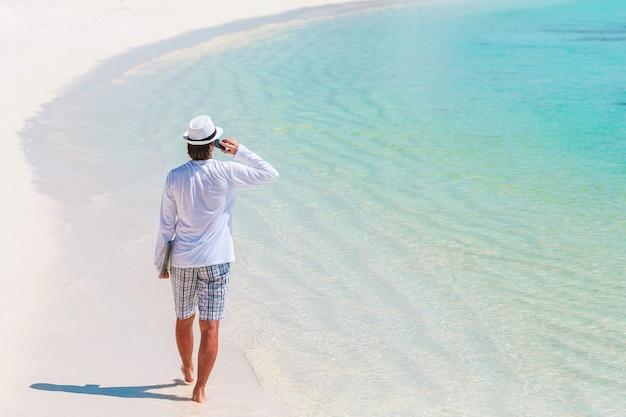 Giovane alla spiaggia tropicale vicino alla villa sull'acqua