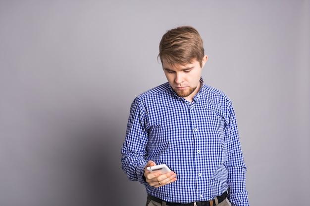 Giovane uomo digitando un messaggio di testo sul suo cellulare contro un muro grigio.