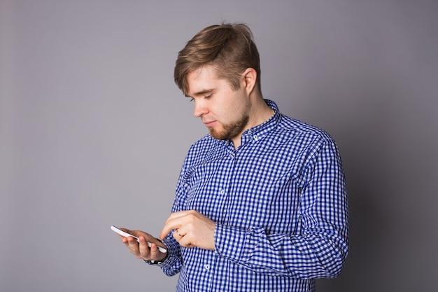 Giovane uomo digitando un messaggio di testo sul suo cellulare contro un grigio